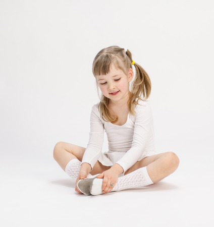 Pretty little girl sitting on the floor and doing exercise, white background photo