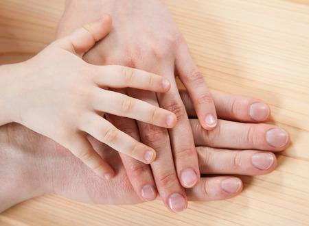 Verenigde handen van vader, moeder en een kind, concept van gelukkige familie