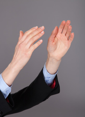 Closeup of human hands applauding on gray background photo