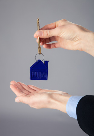 Real estate agents hands holding a key from a house, closeup shot Stock Photo