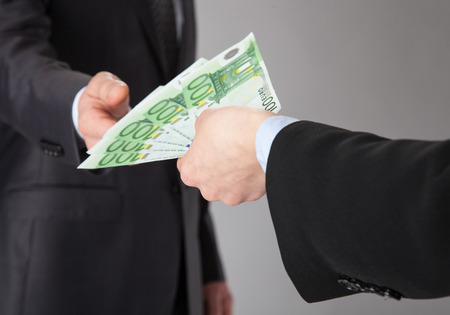 venal: Businessman accepting money offer on grey background