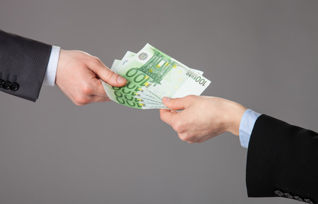 Businesspersons hand accepting an offer of money on grey background photo