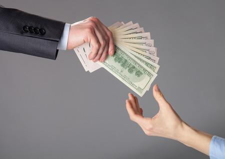 subsidy: Human hands passing fan of dollar banknotes on grey background
