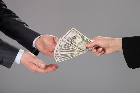 corruptible: Businessmans hands accepting an offer of money on grey background