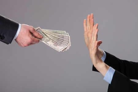Human hands rejecting an offer of money on grey background Stock Photo