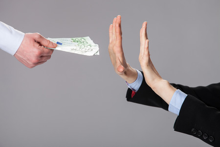 Businessperson's hands rejecting an offer of money on grey background 스톡 콘텐츠
