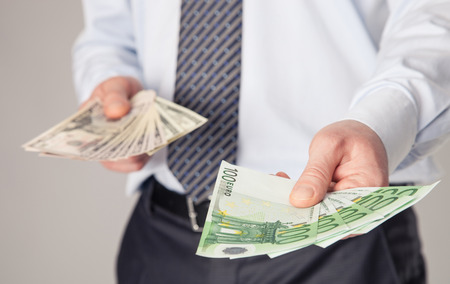 Businessmans hands giving euro and dollar banknotes to you photo