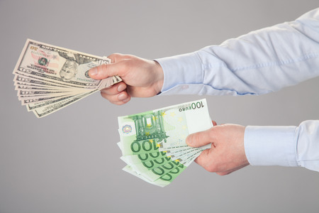 Businessmans hands reaching out dollar and euro banknotes photo