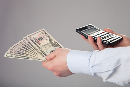Businessmans hands holding dollar banknotes and calculator on gray background photo