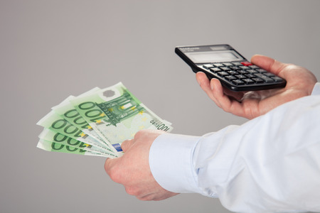 Businessmans hands holding euro banknotes and calculator on gray background photo