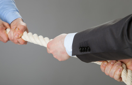 Two businessmen pulling a rope, closeup shot photo