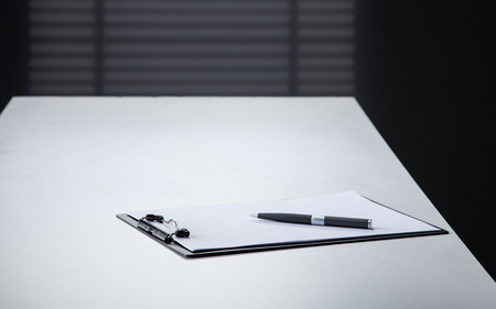 Blank black clipboard with a pen on a white table photo