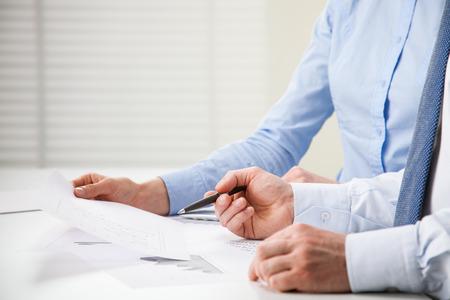 Business mensen bespreking van de financiële grafieken - close-up shot van de handen over tafel