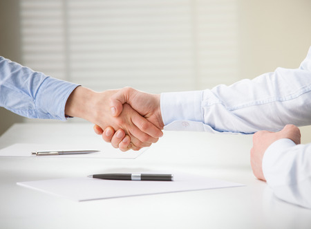 Successful business people shaking hands while making agreement Foto de archivo