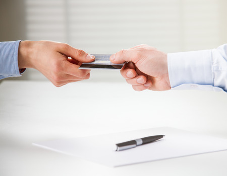 Exchanging credit card over the table with agreement photo