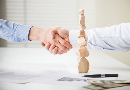 selfcontrol: Business people shake hands near built wooden tower (Japanese game tumi-ishi), illustrating concept of business success, cooperation, achievement and self-control