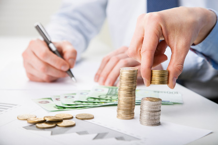 Business people calculating profit - closeup shot of hands counting banknotes and coins and making notes on paper Stock Photo