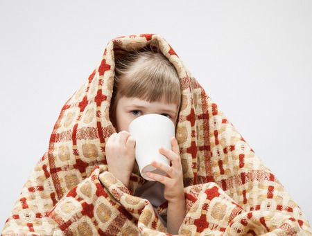 indisposition: Portrait of a little girl covering with a rug and holding a white cup