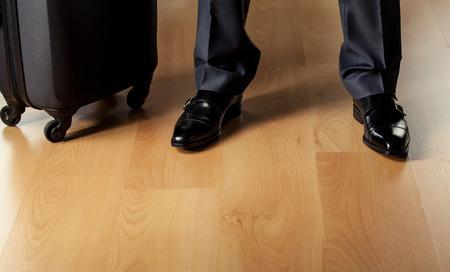 Briefcase and businessmans legs - closeup shot photo