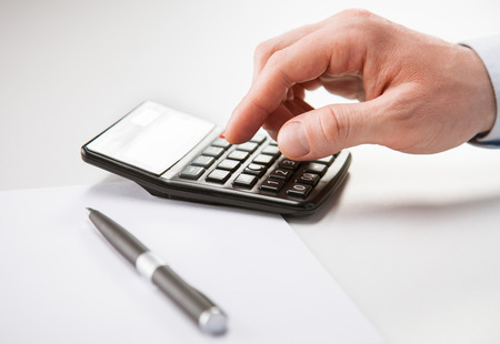 Hand of unrecognizable businessman using calculator - closeup shot photo