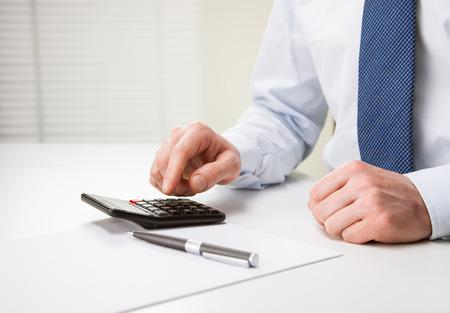 Hands of unrecognizable businessman using calculator - closeup shot photo