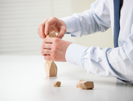 selfcontrol: Businessman making tower of wooden blocks (Japanese game tumi-ishi), illustrating concept of business success, achievement and self-control