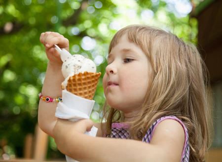 Pretty little girl eating an ice cream outdoors 스톡 콘텐츠