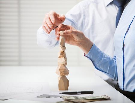 Mensen uit het bedrijfsleven het bouwen van houten toren (Japanse spel Tumi-ishi), illustreren concept van zakelijk succes, samenwerking, prestatie en zelfbeheersing