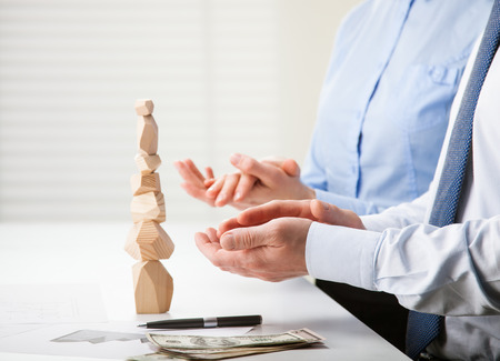 selfcontrol: Business people applauding near built wooden tower (Japanese game tumi-ishi), illustrating concept of business success, cooperation, achievement and self-control Stock Photo