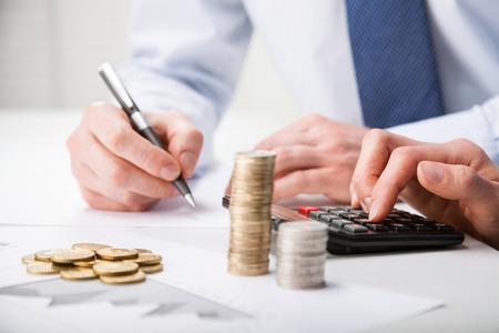 Contadores de cálculo de beneficios - primer disparo de manos contando las monedas y hacer notas sobre el papel Foto de archivo - 31547767