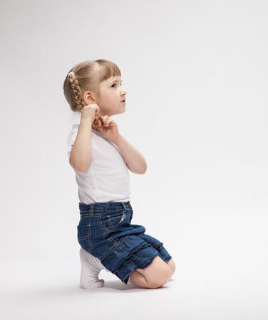 Portrait d'une petite fille assise sur le sol