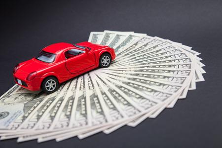 Toy red car on dollars, dark background photo