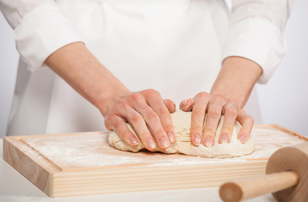 Unrecognizable female cook kneading dough on wooden board photo