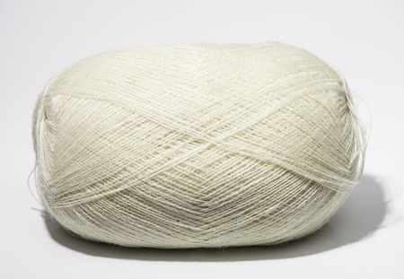 acrylic yarn: One skein of white yarn on neutral background