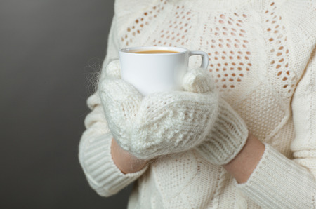 to get warm: Unrecognizable girl feeling cold and holding a cup of hot coffee, grey background Stock Photo