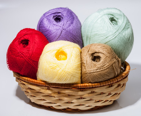 acrylic yarn: Skeins of yarn in a braided basket on neutral background