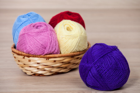 acrylic yarn: Skeins of yarn in a braided basket on wooden background Stock Photo