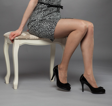 Legs of young woman wearing mini dress and high-heeled black shoes, gray background photo