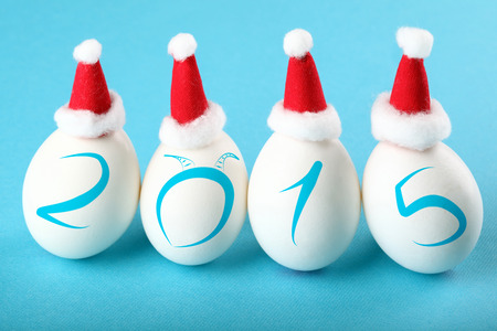 Birth of a new year. Four eggs in Santas hats on blue background with 2015 numbers and Goat horns photo