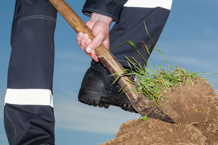 uniform green shoe: Farmer digging a garden - closeup shot Stock Photo