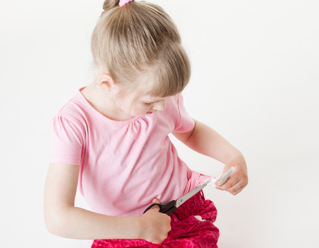 brand label: Little girl snipping off a brand label, white background