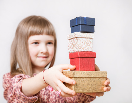 neutral background: Pretty little girl holding gift boxes on neutral background