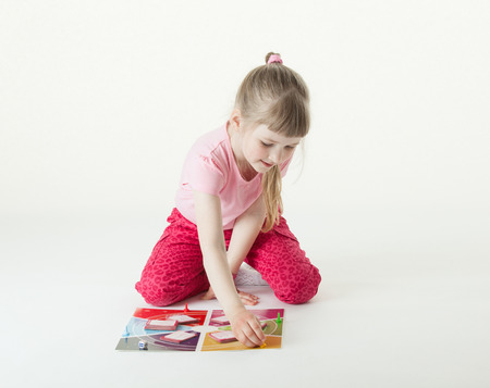 intrest: Charming little girl playing on the floor, white background