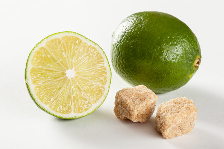 cane sugar: Ripe limes and pieces of unrefined cane sugar, neutral background