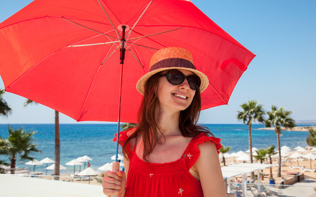 sundress: Happy young woman in a red sundress with a red umbrella on seafront background