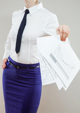 disregard: Strict unrecognizable businesswoman holding documents carelessy , neutral background