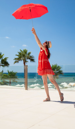 unconcerned: Happy young woman in a red dress with a red umbrella on seafront background
