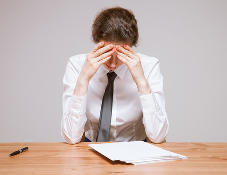 weary: Weary businesswoman on workplace, neutral background