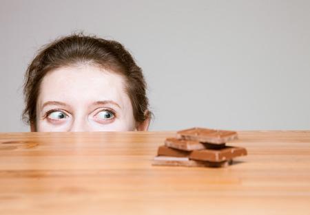 Jonge vrouw te willen melkchocolade eten, neutrale achtergrond