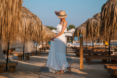 beach feet: Young woman in a white sundress and hat  walking by the beacn
